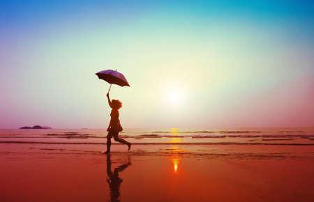 gelukkige vrouw springen met paraplu op het strand Stockfoto