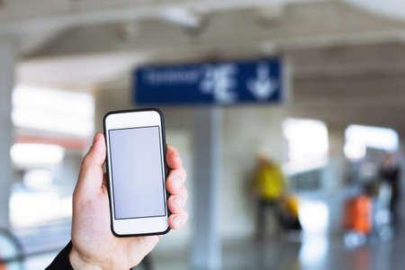 hand houden van smartphone met een leeg scherm in de luchthaven Stockfoto