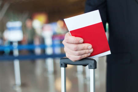 boarding card: close up of passport and ticket in hand in airport