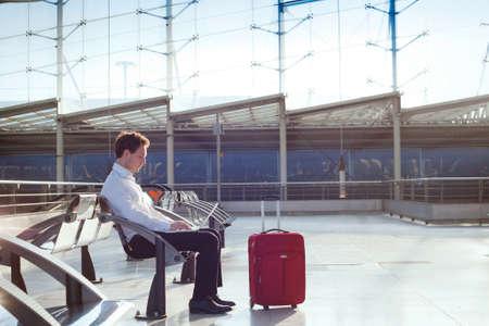 ノート パソコンを空港で待っているビジネスマン 写真素材