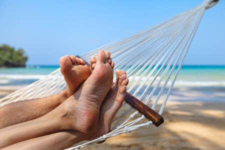 in hammock: happy couple on the beach in honeymoon