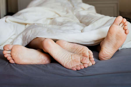 young sex: ноги любовника в постели Фото со стока