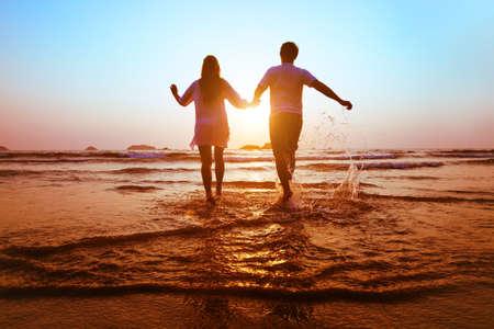 luna de miel: joven pareja feliz se ejecutan al mar en la playa de la puesta del sol