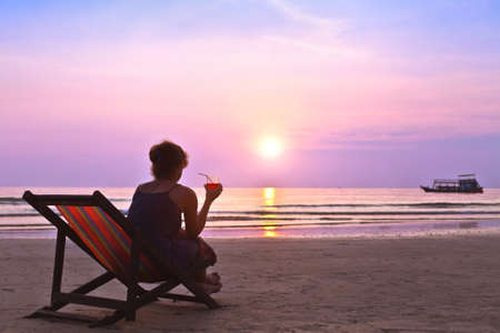 middle age woman with cocktail enjoy sunset on the beach