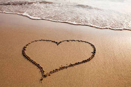 Heart drawn on the sandy beach, valentines day background
