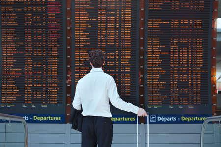 passagier kijken naar tijdschema boord op de luchthaven