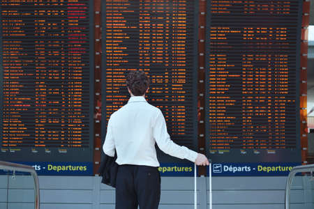 departure board: passenger looking at timetable board at the airport Stock Photo