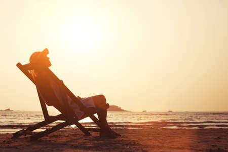 열 대 해변에서 젊은 여자를 즐기고 일몰