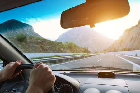 hombre conduciendo: Conducción de automóviles en la carretera de montaña Foto de archivo