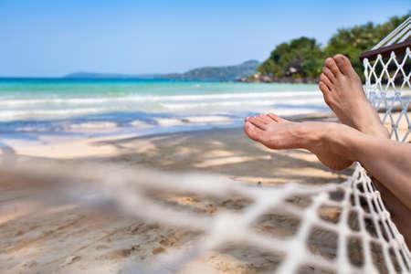 arena: pies de la mujer en la hamaca en la playa