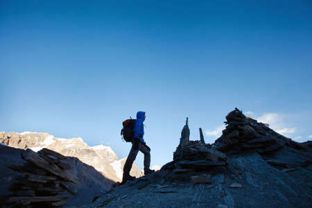 silhouette of hiker climbing mountain peak at sunrise