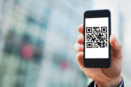 hand holding smartphone with QR code on the screen Reklamní fotografie