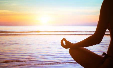 spirit: meditation concept, yoga practice on the beach at sunset