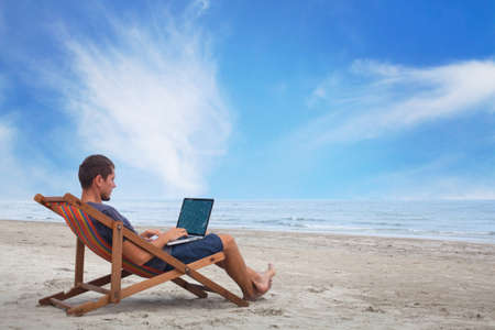 해변에서 컴퓨터로 작업하는 사업가 스톡 콘텐츠