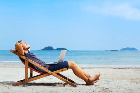 hombre de negocios sonriente con la computadora relajarse en la playa Foto de archivo