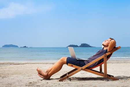 happy business man with laptop relaxing on the beach