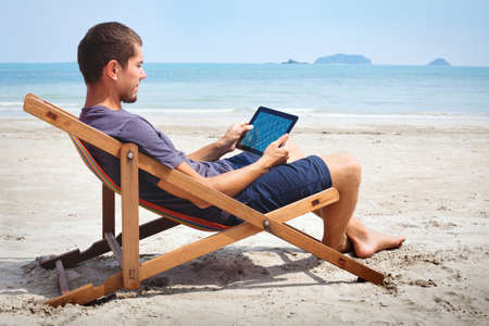 business man working with tablet on the beach