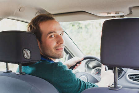 portrait of driver in the car or taxi, young caucasian man Standard-Bild