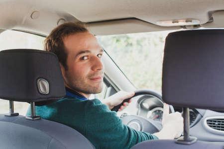 Portret van bestuurder in de auto of taxi, jonge Kaukasische man