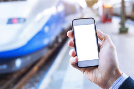 france station: hand holding smartphone with empty blank screen in train station