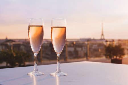 エッフェル塔とパリのスカイライン、高級のカップルのためのロマンチックなディナーを望む屋上のレストランでシャンパンを 2 杯