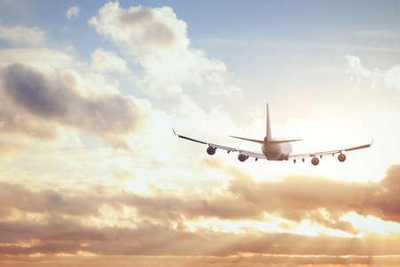 夕焼け空に飛行機 写真素材