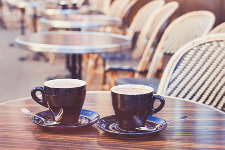 two cups of hot chocolate or coffee cappuccino on the table in cafe, close up, vintage style