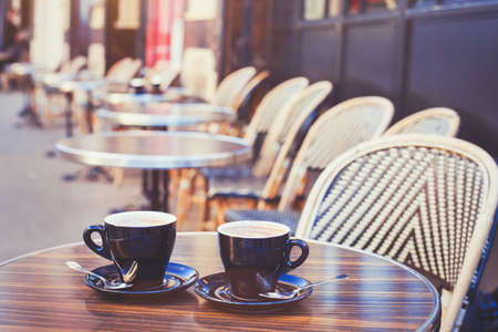 macchiato: street cafe in Europe, two cups of coffee on cozy vintage terrace