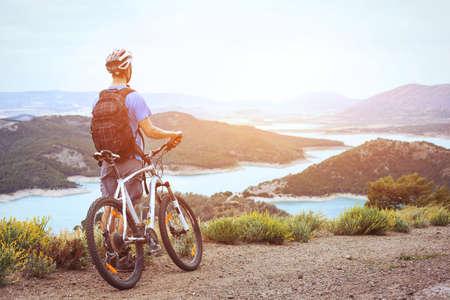 cycling, mountain biking, man with bicycle enjoying panoramic view at sunset