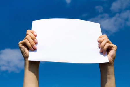 blank page in hands on blue sky background