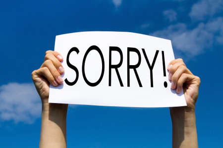 sorry, concept, hands holding sign in blue sky Stock Photo