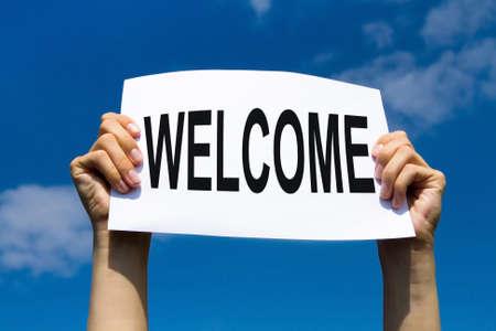 コンセプトを歓迎、紙を開いて手に青い空に署名