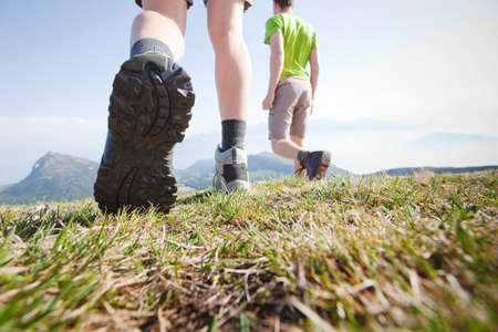 hikers walking in the mountains, close up of the foot, low angle Stock Photo