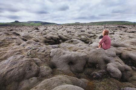 woman sitting alone in the lava field, looking at the sky and thinking about life meaning Stock Photo