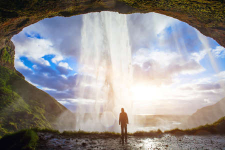 incredible waterfall in Iceland, silhouette of man enjoying amazing view of nature Banco de Imagens