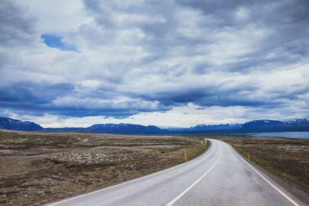 背景には、アイスランドの劇的な風景の中の美しいアスファルトの道路の旅行します。 写真素材