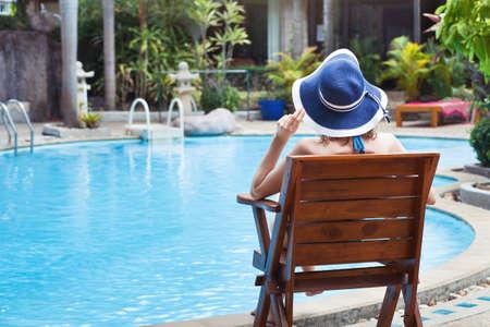 夏休み、プールの近くの美しい高級ホテルでリラックスできる女性