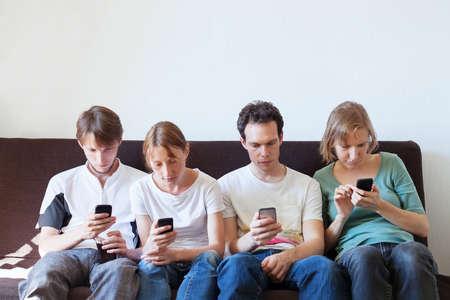 Internetverslaving, groep jonge mensen die naar hun smartphones kijken