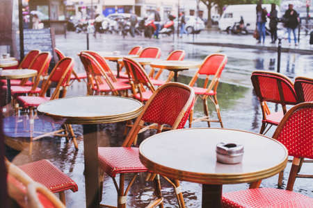 street cafe in Paris in rainy day, red wicker chairs and tables
