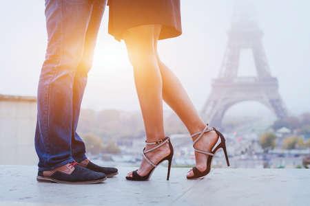 romantische vakantie in Parijs, voeten van het paar kussen in de buurt van de Eiffeltoren