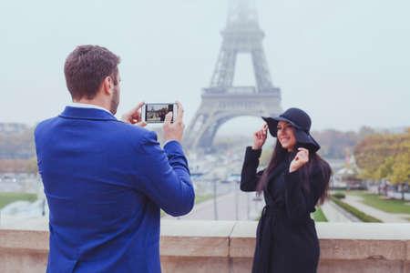 モバイル写真、男彼の電話、パリ、フランスのエッフェル塔近く観光客のカップルを持つ女性の写真を撮影 写真素材