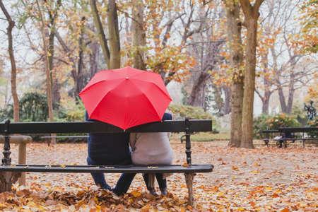 秋の公園での傘の下のカップル