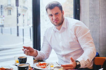 displeased angry customer in restaurant, man unhappy with food and bad service Stock Photo