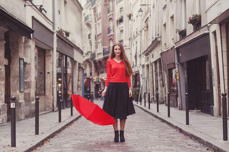 Hermosa mujer, retrato de niña con paraguas rojo de pie en la calle de París Foto de archivo - 77018089