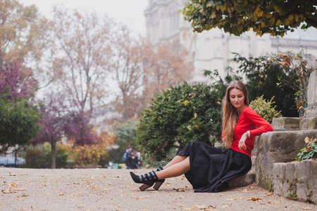 beautiful woman in red, portrait of caucasian fashion young model with long hair sitting alone, psychology concept