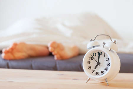 alarm clock and feet of sleeping person, morning concept, wake up Stock Photo