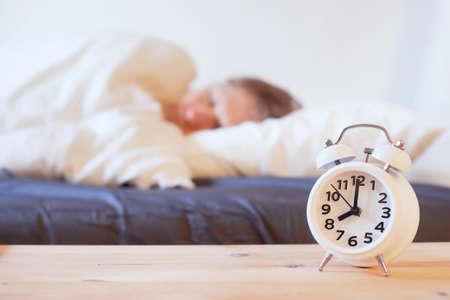 目覚まし時計、ベッドで眠っている人のある朝、目を覚ます