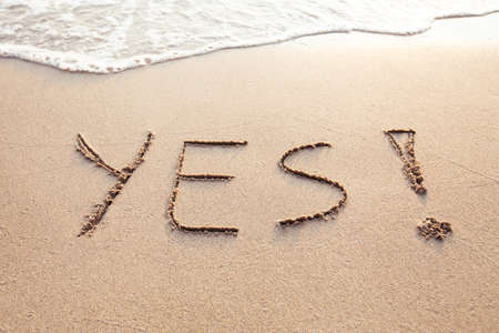 YES concept, positive changes in the life, word written on sand beach Foto de archivo