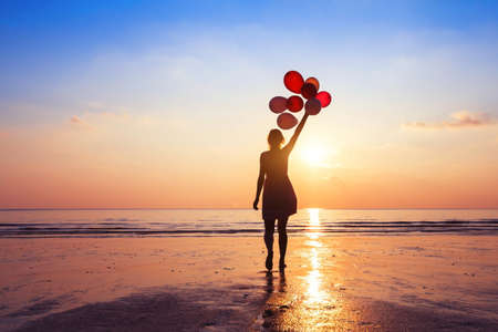 motivation or hope concept, follow your dream and inspiration, girl with balloons at sunset Фото со стока
