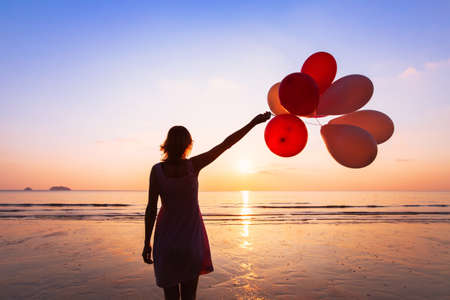 imagination and creativity, girl with multicolored balloons at sunset with copyspace, inspiration concept